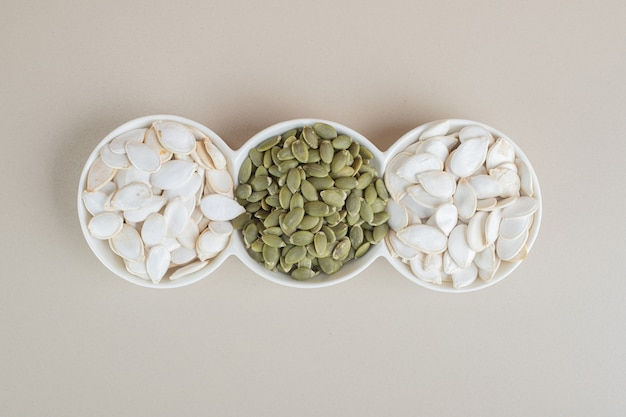 White and green pumpkin seeds in white cups.