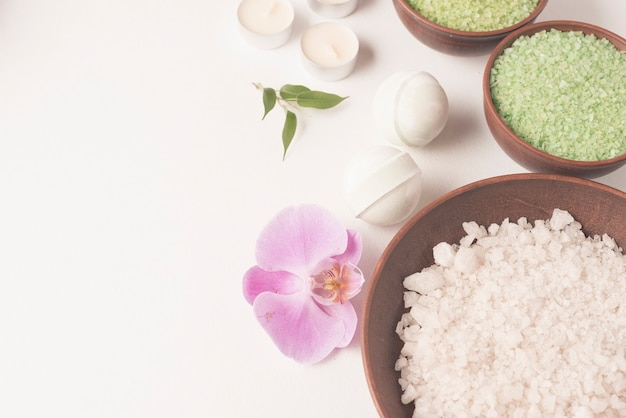 White and green spa bath salt bowl with spa bomb and orchid on white backdrop