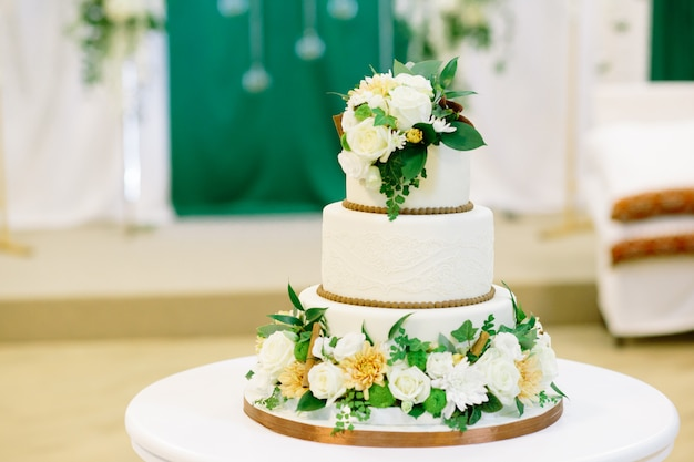 White and green wedding cake with flowers at reception