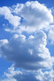 White and grey cumulus clouds on blue sunny sky