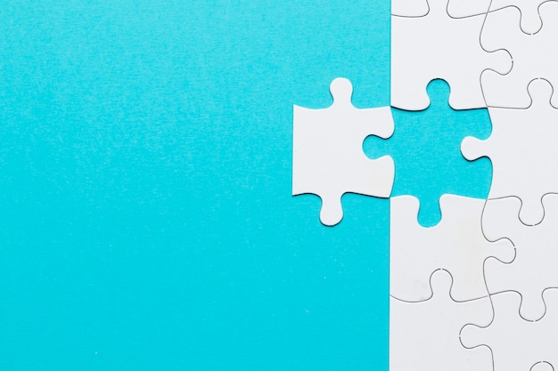 Головоломка в виде белой сетки с отсутствующим кусочком головоломки на синем фоне