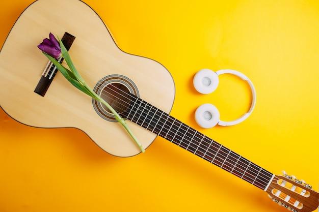 Белая гитара и белые беспроводные наушники на оранжевом фоне, весенние цветы, букет фиолетовых тюльпанов, белая гитара и цветы, весенний музыкальный плакат.