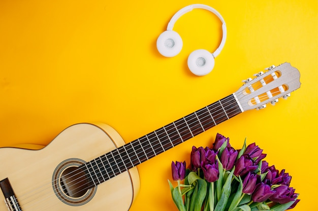 White guitar and white wireless headphones on the orange background, spring flowers, bunch of purple tulips, white guitar and flowers, spring music poster.