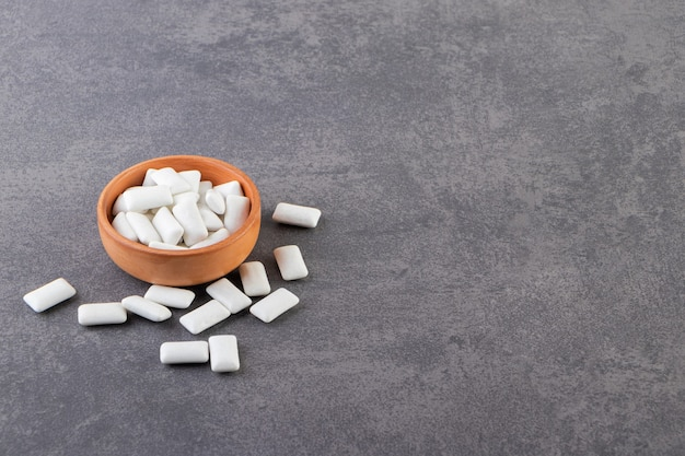 White gums on grey background and in bowl .