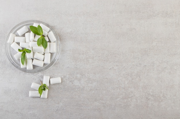 White gums with mint leaves in glass bowl.
