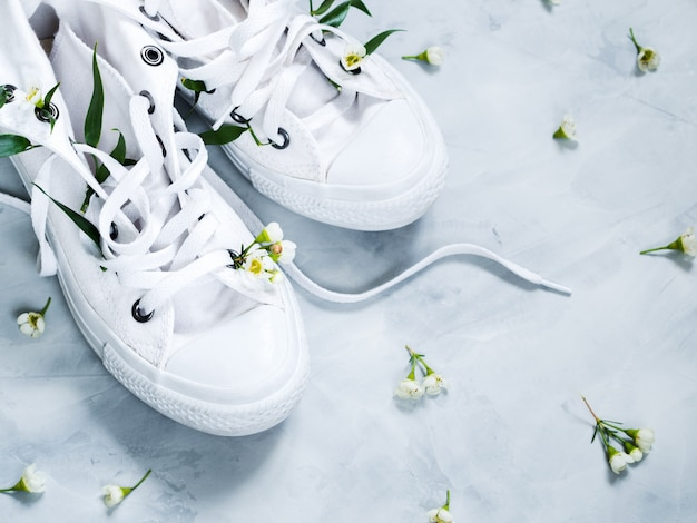 White gumshoes with fresh flowers on grey background