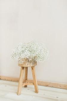 淡いパステル ベージュの背景に木製の背中の開いたスツールに白いカスミソウの花の花束。最小限のお祝いホリデー コンセプト