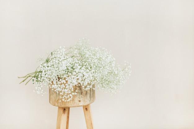 淡いパステル ベージュの背景に木製の背中の開いたスツールに白いカスミソウの花の花束