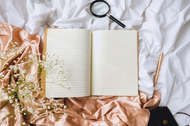 White gypsophila flowers, notebook, pen on the bed. white sheet and gold satin fabric.