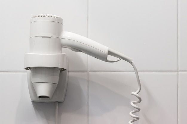 White hair dryer on the wall in bathroom with white tiles