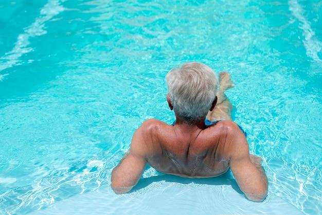 青い水のプールで夏休みを楽しんでいる白い髪の男