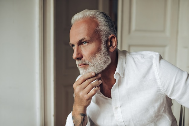 L'uomo dai capelli bianchi in camicia posa pensieroso in un appartamento luminoso
