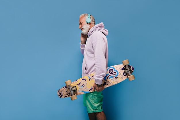 Uomo dai capelli bianchi in abito street style che ascolta musica e tiene in mano lo skateboard
