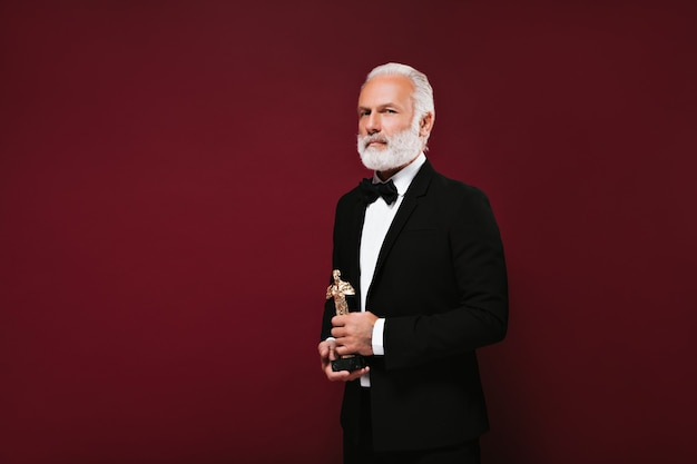 White haired man in suit looks into camera and holds oscar statuette
