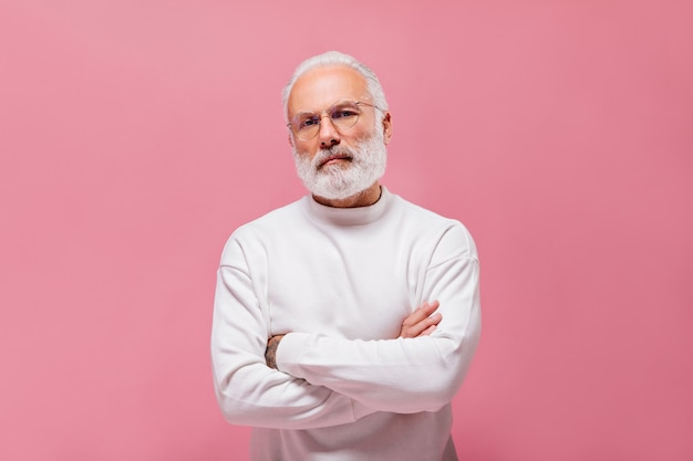 White haired man in sweater and eyeglasses posing on pink wall
