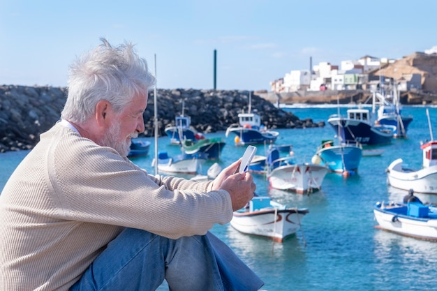 White-haired senior man sitting at the port smiles looking at his smartphone. attractive people enjoying the outdoors and the beauty of nature. fishing boats and coast in the background