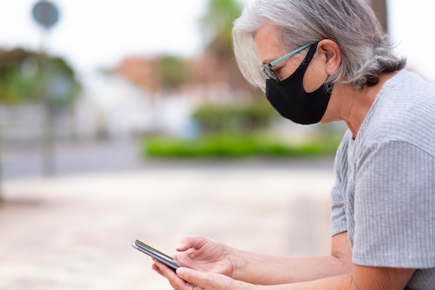 A white-haired senior woman with medical mask due to coronavirus sitting in a public park using her mobile phone - relaxed retirement concept