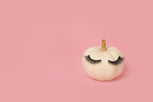 Белая тыква хэллоуина с макияжем ресниц. минимальная концепция курортного сезона розовый фон.