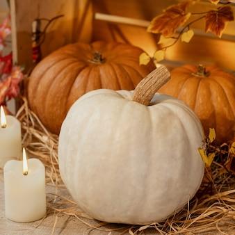 キャンドル、わら、秋の紅葉と木箱で白いハロウィンのカボチャ
