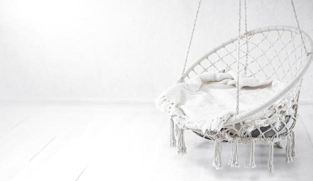 白い壁に白いハンモックチェア。週末の居心地の良い場所は、部屋のコピースペースでリラックスしてください。