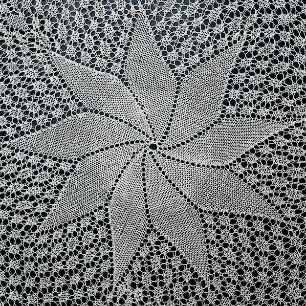 White hand knitted lace on black surface.
