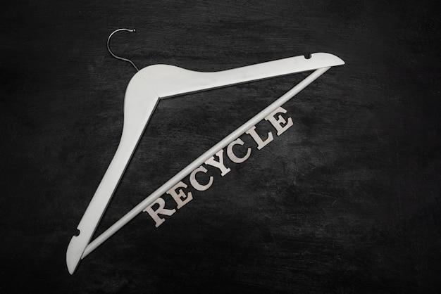 흰색 옷걸이와 비문 검은 표면에 재활용. 재활용. 친환경 의류 소비.
