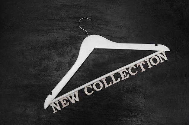 黒の背景に白いハンガーと新しいコレクションの碑文。ファッションワードローブ。