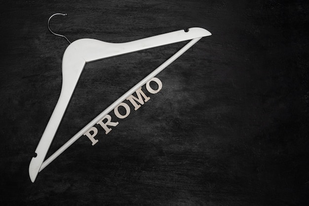 White hanger and inscription promo on black background. shares, discounts.