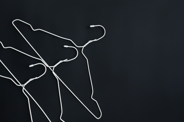 White hangers on black paper background.