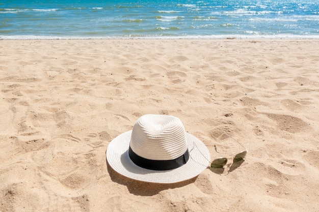 White hat and sunglasses on beach, summer concept