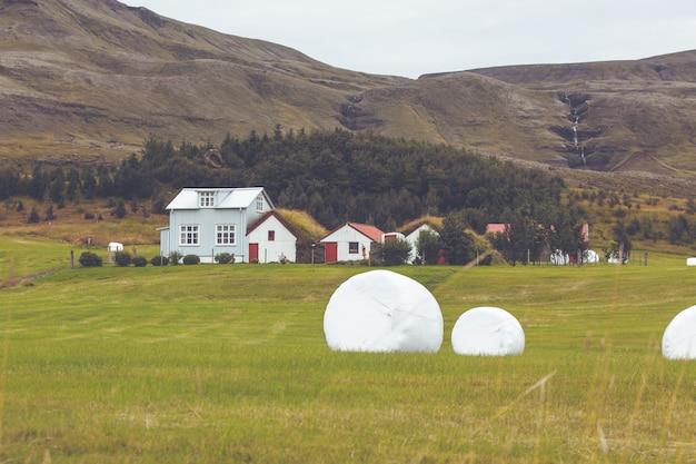 Белые рулоны сена на зеленом поле исландии. горизонтальный снимок
