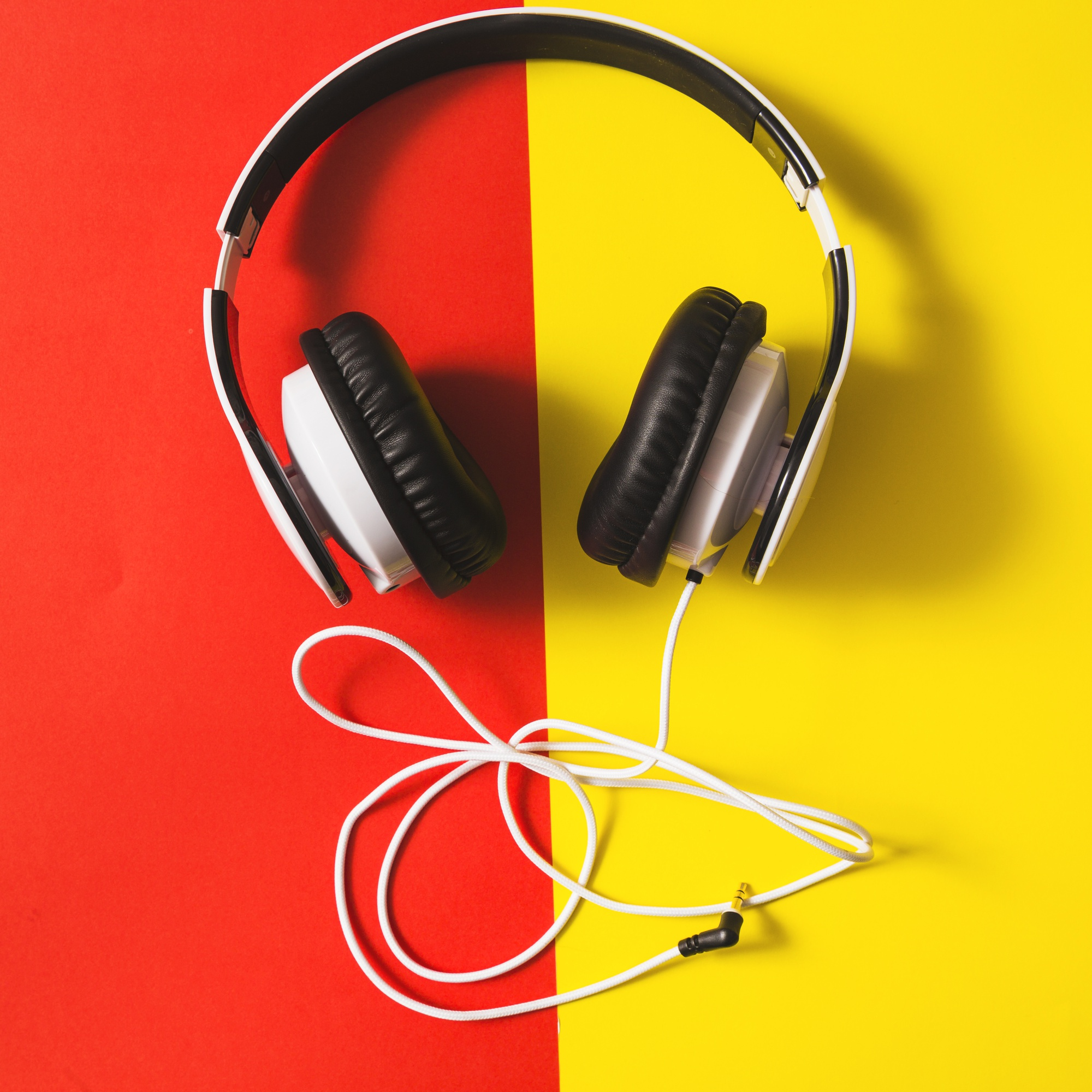White headphone over the dual red and yellow background