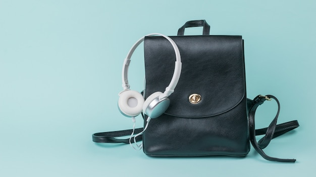 White headphones and a black leather backpack on blue