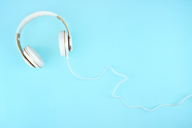 White headphones on blue background with copy space. flat lay. music concept.