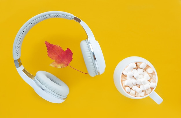 White headphones, cup with coffee and marshmallows and a red-yellow leaf on bright yellow, flat lay