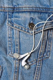 Белые наушники для телефона на поверхности джинсовой куртки. крупный план.