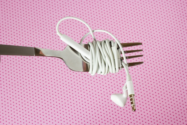 White headphones and fork on a pink background with polka dotsd, close-up