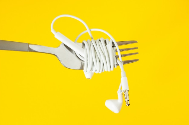 White headphones and fork on a yellow background
