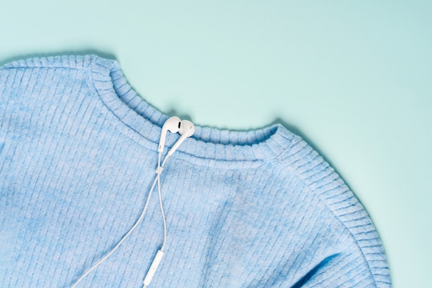 White headphones lie on a blue knitted sweater on a pastel background