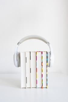 Белые наушники на стопке из 5 книг на столе на фоне белой стены. концепция аудиокниги. копировать пространство.