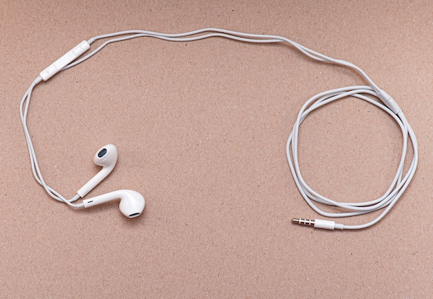White headphones on soft brown paper with space for text or ideas, wire and earphones