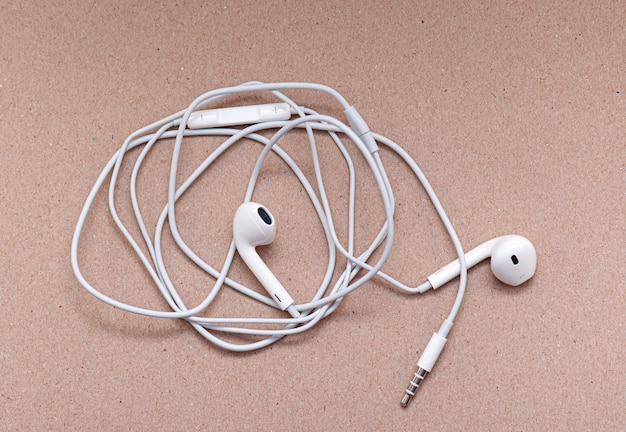 White Headphones On Soft Brown Paper With Space For Text Or Ideas Wire And Earphones Premium Photo