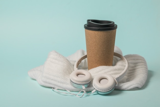 White headphones and a white scarf with a paper cup of hot coffee. winter mood.