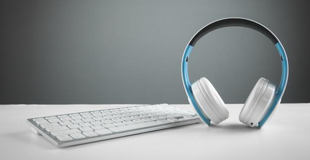 コンピューターのキーボードと白いヘッドフォン。ビジネスデスク