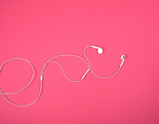 White headphones with a cable on a pink background