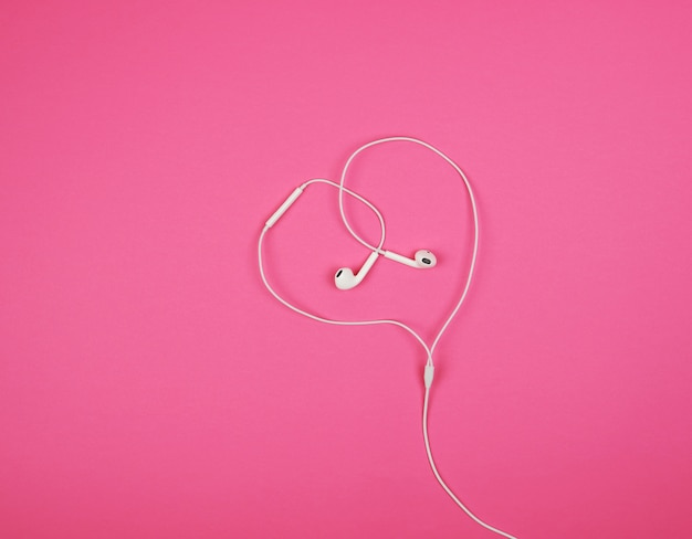 White headphones with a cable on pink