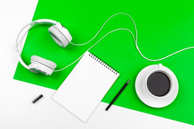 White headphones with cord on bright green