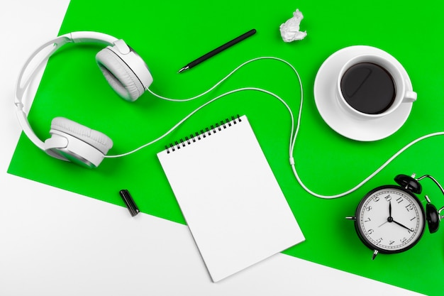 White headphones with cord, coffee cup, alarm clock and black notebook