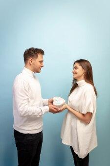 白い心。青いスタジオの壁に恋をしている美しいカップル