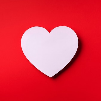White heart cutted from paper over red background with copy space. valentine's day. love, date, romantic concept.
